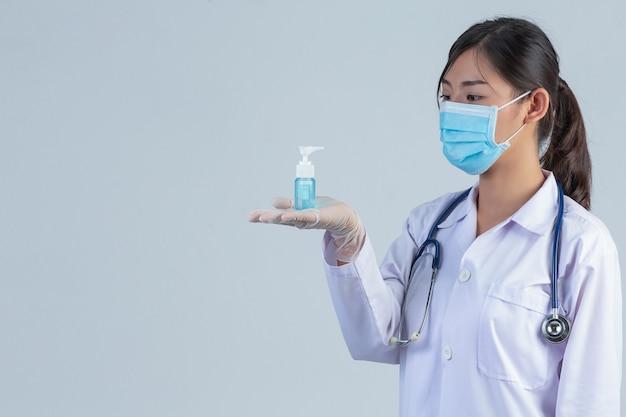 美しい若い医者は灰色の壁にゲルを手で押しながらマスクを着ています。