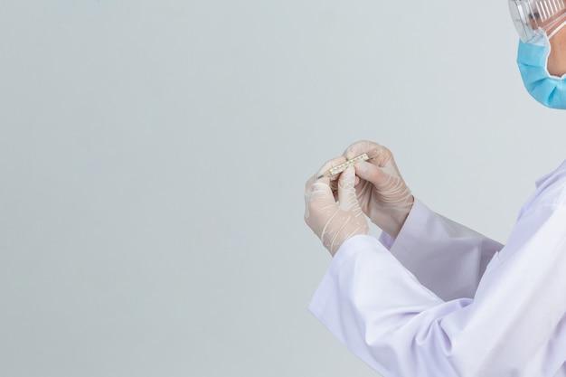 Il bello giovane medico sta indossando la maschera mentre tiene il termometro con i guanti di gomma sulla parete grigia.