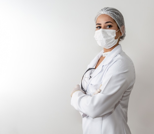 Beautiful young doctor woman in medical white coat and a protective mask and rubber gloves.