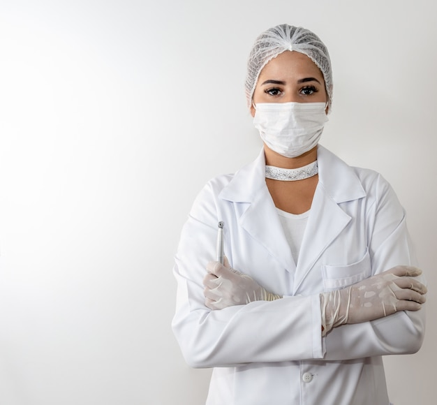 Beautiful young doctor woman in medical white coat and a protective mask and syringe.
