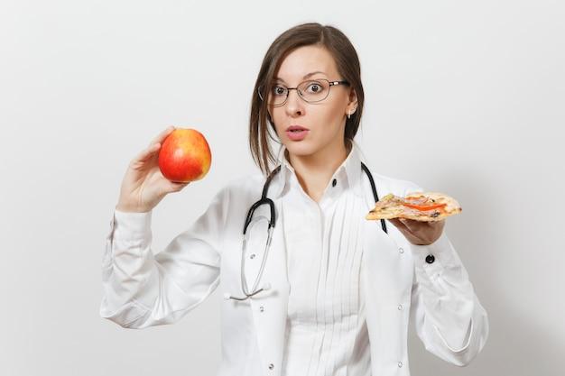 청진 기 흰색 배경에 고립 된 아름 다운 젊은 의사 여자. 빨간 사과 피자 조각을 들고 의료 가운에 여성 의사. 의료 직원 건강 개념 적절한 영양을 선택하십시오.