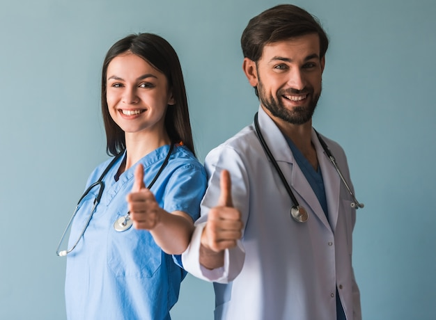 Beautiful young doctors are showing thumbs.
