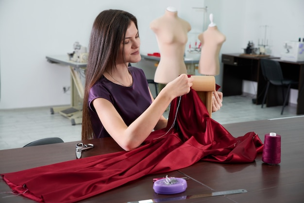 Beautiful young dressmaker in workroom sewing red dress in tailor studio or atelier shop