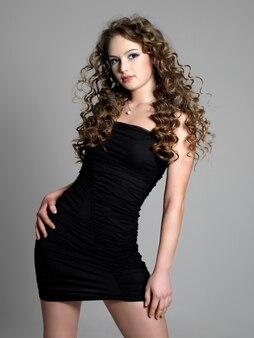 Bella giovane donna di eleganza in vestito nero