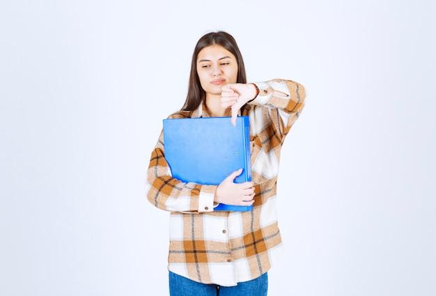親指を下に与える青いフォルダーを持つ美しい若い従業員。