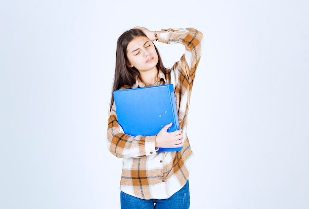 Beautiful young employee with blue folder having headache.