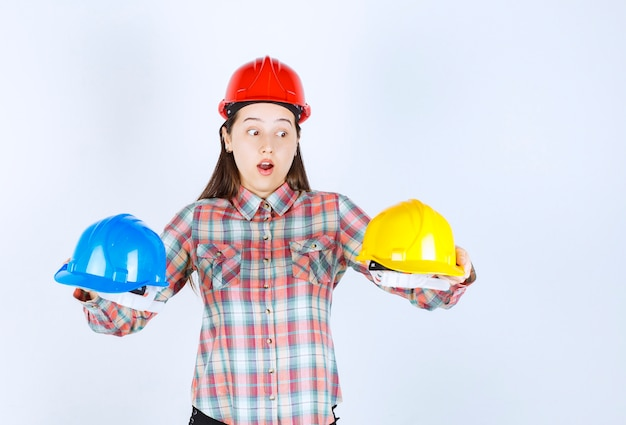 Beautiful young engineer holding security helmets and standing on white background.