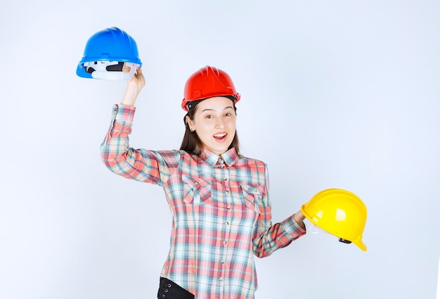 Beautiful young engineer holding security helmets on white background.