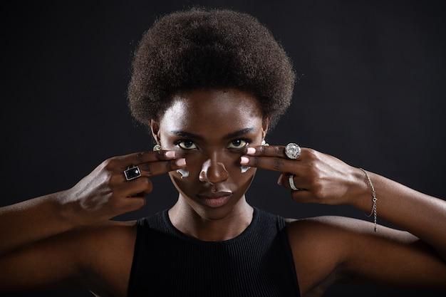 Красивая молодая афро-американская чернокожая женщина, наносящая увлажняющий крем с белым кремом на лицо