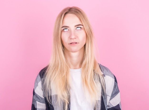 Beautiful young european blonde woman jumping on a pink background in a checkered shirt
