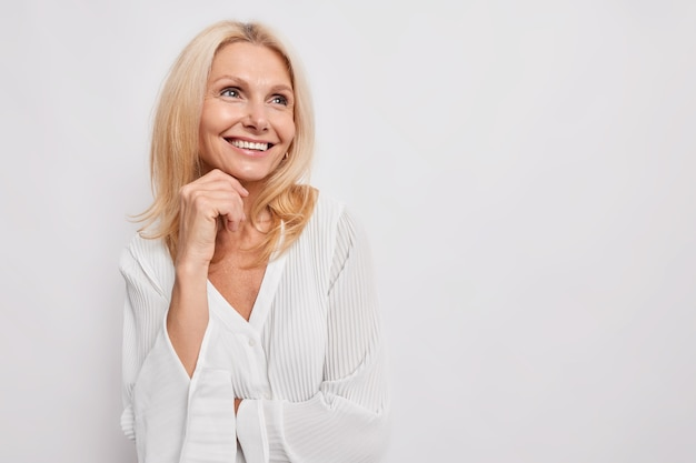 중년의 아름다운 젊은 유럽 여성은 광고를 위해 흰 벽 복사 공간 위에 격리된 실크 블라우스를 입고 꿈꾸는 듯한 표정으로 턱 아래 손을 부드럽게 유지합니다.