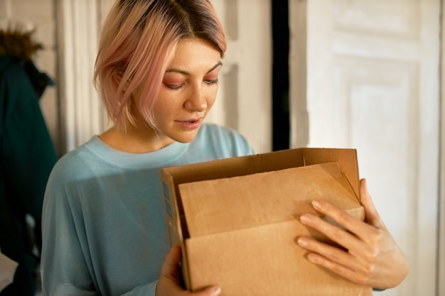 Beautiful young european woman posing indoors with cardboard box in her hands, opening it, looking inside.