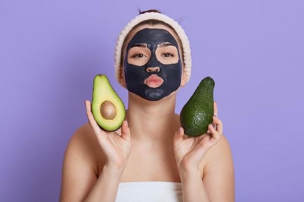 黒の顔のマスクと手に新鮮なアボカドを持つ美しい若いヨーロッパの女性