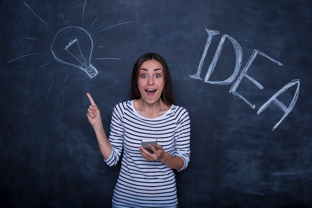 Beautiful young excited woman is posing on a chalkboard background with a lamp idea picture.