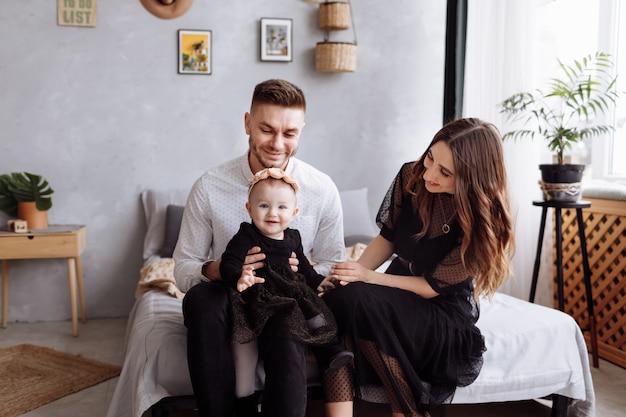 美しい若い家族は、スタイリッシュなベッドルーム、ママ、パパ、女の赤ちゃんを自宅のベッドに座っています。母の日、父の日、赤ちゃんの日。一緒に時間を過ごす家族。家族の一見。セレクティブフォーカス