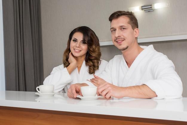 Beautiful young family couple in white bathrobes enjoying honeymoon at hotel