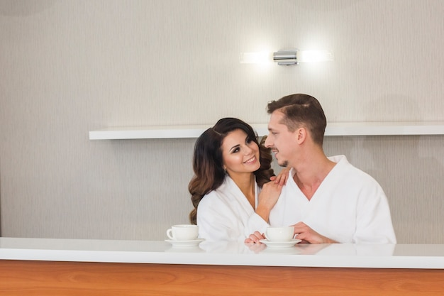Beautiful young family couple in white bathrobes enjoying morning tea in hotel