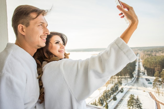 Beautiful young family couple in white bathrobes have fun take selfie on terrace