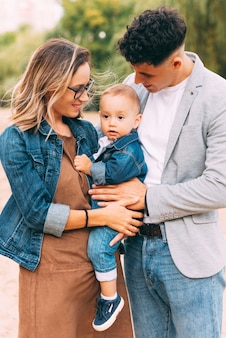 美しい若い家族は公園で楽しい時間を過ごしています