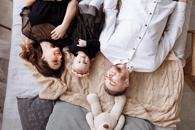一緒に自宅のベッドに横たわっている美しい若い家族、ママ、パパと赤ちゃんの女の子、トップビュー。母の日、父の日、赤ちゃんの日。一緒に時間を過ごす家族。家族の一見。セレクティブフォーカス