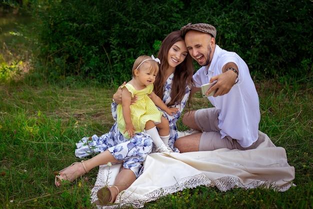 Красивая молодая семья делает селфи на пикнике. родители с маленькой дочкой фотографируют на мобильный телефон в зеленом парке