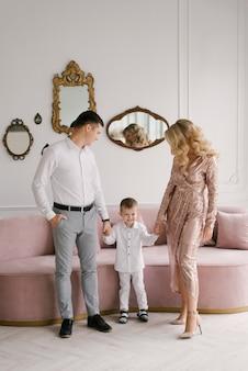 豪華な明るいインテリア、幸せな家族のスマートな服を着た美しい若い家族の男性の女性と息子