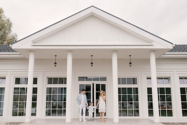 豪華な白い家の背景にスマートな服を着た美しい若い家族の男性の女性と息子