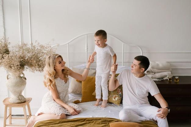 白い服を着た美しい若い家族の男性の女性と息子が自宅のベッドで遊ぶ