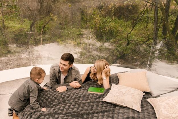 美しい若い家族の男性の女性と息子は、料理、ピクニック、キャンプ用のベッドとストーブ付きの大きな丸いテントで自然の森でリラックスします