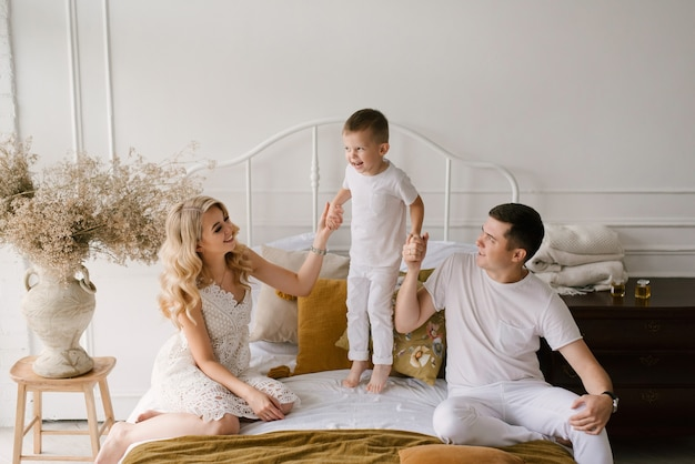 Beautiful young family man woman and son in white clothes play on the bed at home