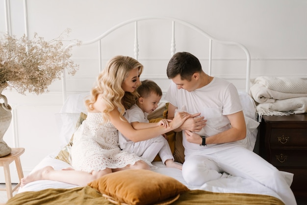 Beautiful young family man woman and son in white clothes play on the bed with a rabbit at home