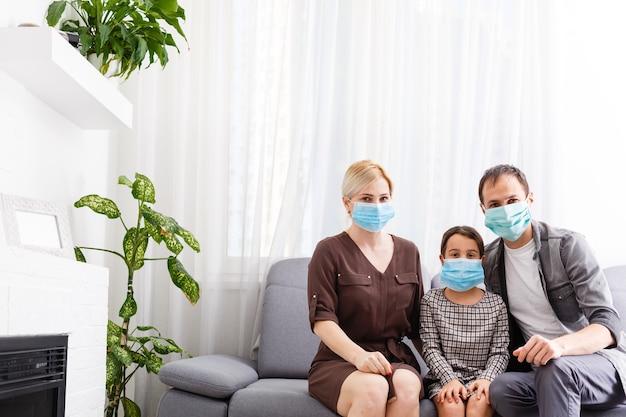 コロナウイルスの世界的大流行に対してフェイスマスクを着用し、家にいる美しい若い家族