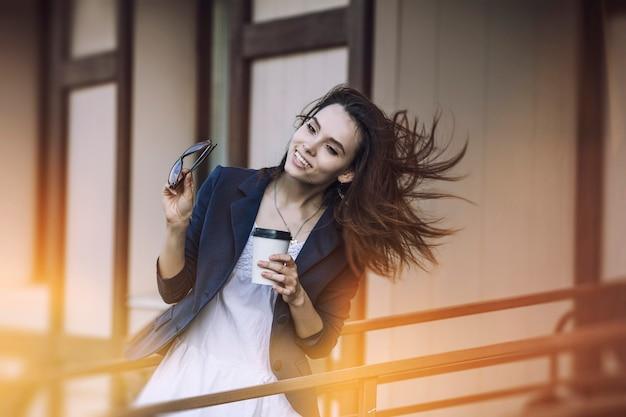 美しい若いファッションの女の子は、持ち帰り用のコーヒーを手にカフェから来ています