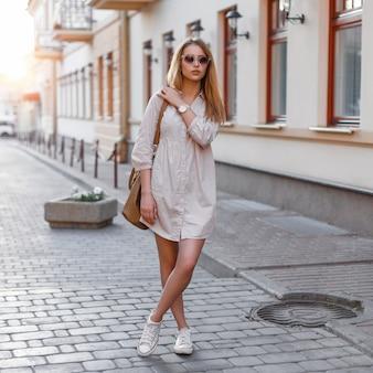 サングラス、ハンドバッグ、スニーカーの美しい若いファッションの女の子