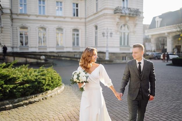Красивая молодая модная стильная пара идет по улице в городе