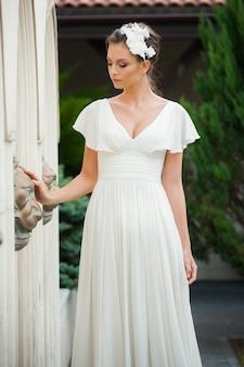 街の明るい白いドレスの夏の美しい若いファッションの女性