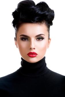 赤い口紅を持つ美しい若いファッションの女性。明るい光沢のメイクアップポーズのグラマーファッションモデル。