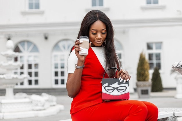 白い建物の近くの街でコーヒーとトレンディなバッグと赤いスタイリッシュなスーツできれいな肌を持つ美しい若いファッショナブルな黒人女性。アフリカの女の子モデルは、通りのベンチで休憩し、おいしい飲み物を飲みます。