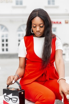 Beautiful young fashionable black woman with clean skin in red stylish suit with trendy bag in city near white building. african girl fashion model resting on bench on street on spring day.
