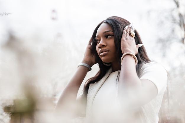 花の近くの公園で白いスタイリッシュな服を着たきれいな肌を持つ美しい若いファッショナブルな黒人女性は、歩きます。春の日に自然の中で休んでいるアルフィカンの女の子。