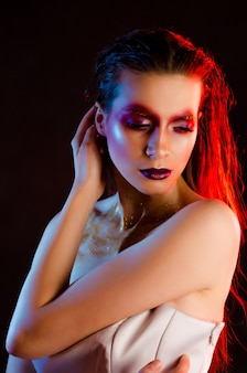 Beautiful young fashionable girl with art make-up in color light
