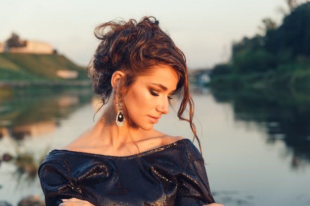 Beautiful young fashionable woman posing in dress at the river coast