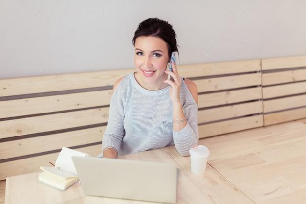 コーヒーカップの隣の机でラップトップコンピューターで作業しながら携帯電話を持つ美しい若い女性の大人