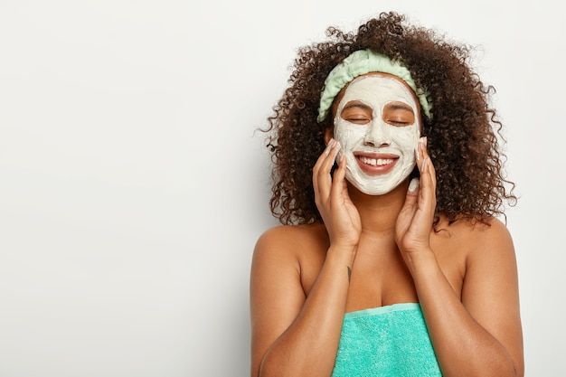 Beautiful young female applies white facial clay mask, has rejuvenation treatments in spa salon, wears headband, stands with turquoise soft towel around naked body, cleans skin