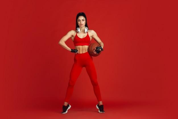 、モノクロの赤い肖像画で練習している美しい若い女性アスリート。ボールとヘッドフォンを備えたスポーティなフィットブルネットモデル。ボディービル、健康的なライフスタイル、美しさとアクションのコンセプト。