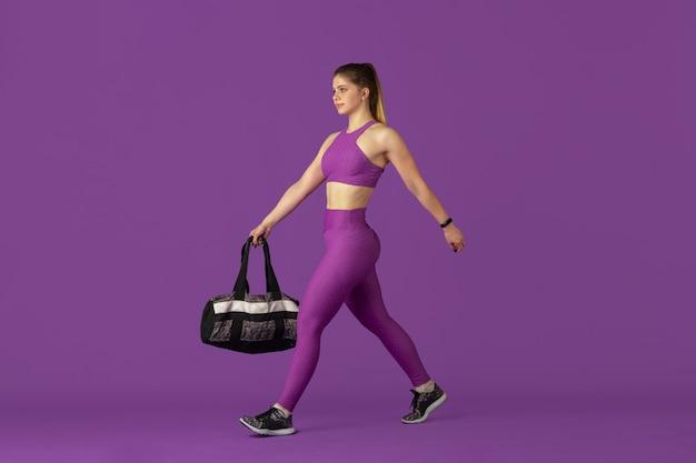 스튜디오에서 연습하는 아름다운 젊은 여성 운동선수, 단색 보라색 초상화.