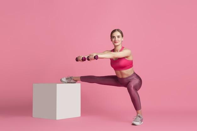 Красивая молодая спортсменка, практикующая в розовой студии