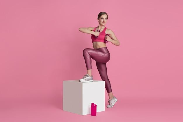 Красивая молодая спортсменка, практикующая на розовой стене монохромный портрет
