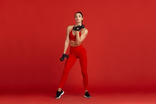 Красивая молодая спортсменка упражнениями на красной стене студии