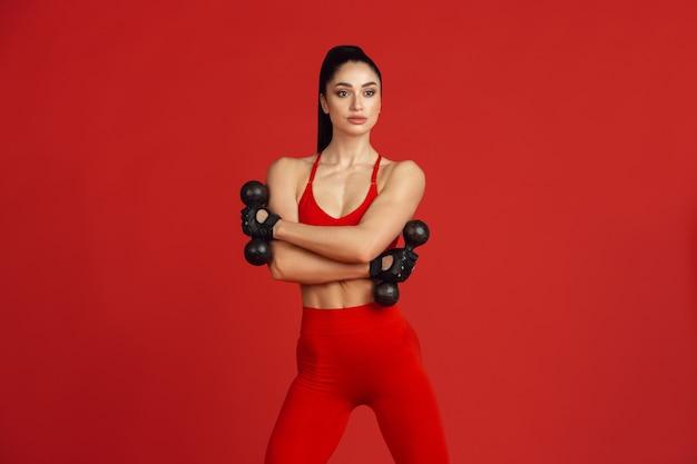 赤いスタジオの壁で練習している美しい若い女性アスリート